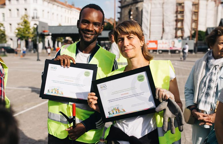 Two volunteers with certificates after clean-up event.