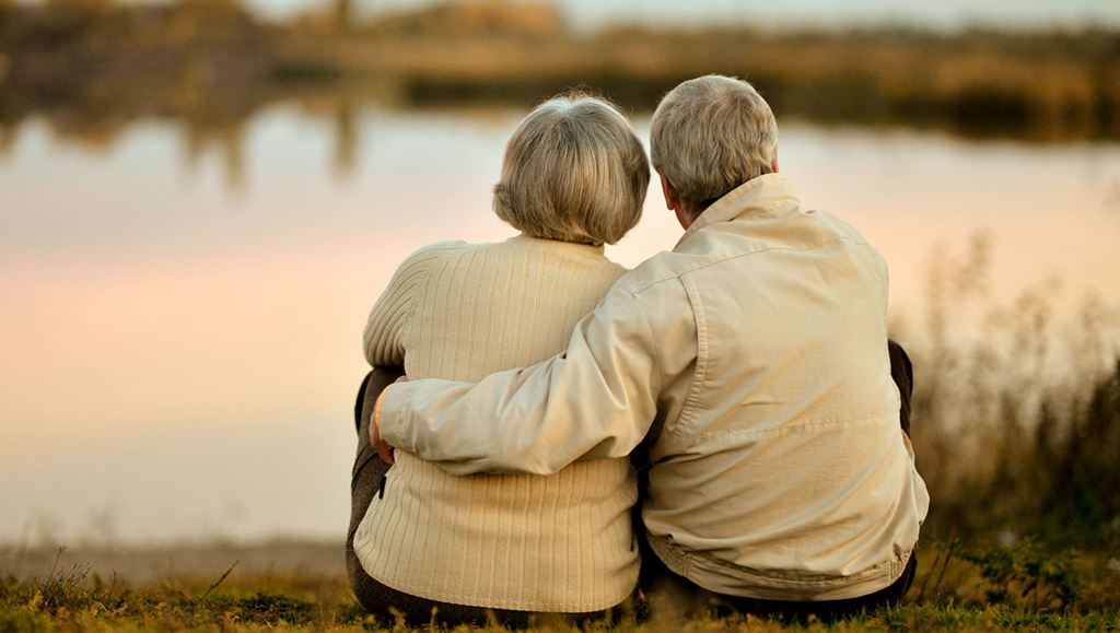Elderly couple embracing looking out at a lake