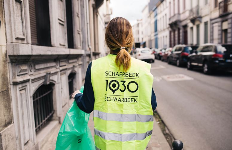 Person collecting rubbish on Schaerbeek streets wearing campaign jacket.
