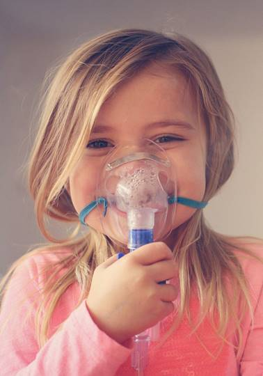 Little girl using inhaler and showing OK.