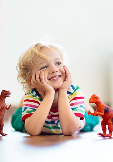 Child playing with dinosaur toys