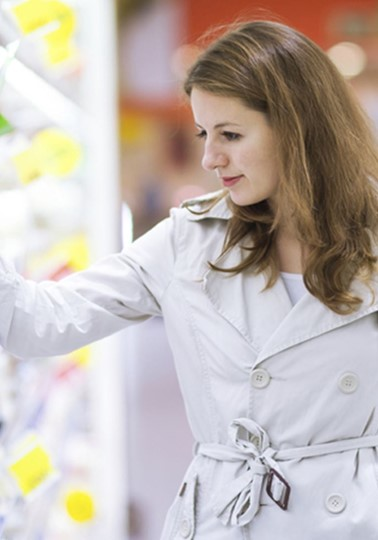 Girl at supermarket, looking at food on shelves