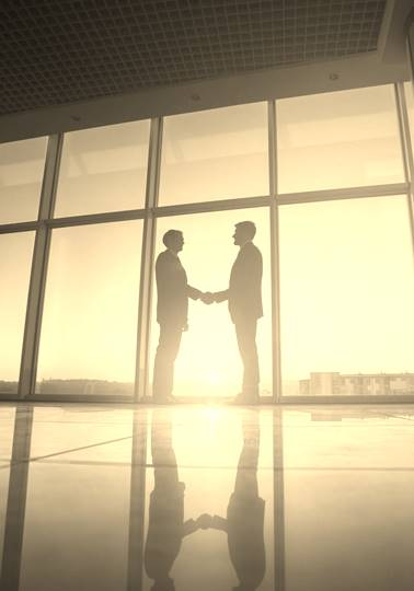 Two businessmen handshake in the office on the bright sun background